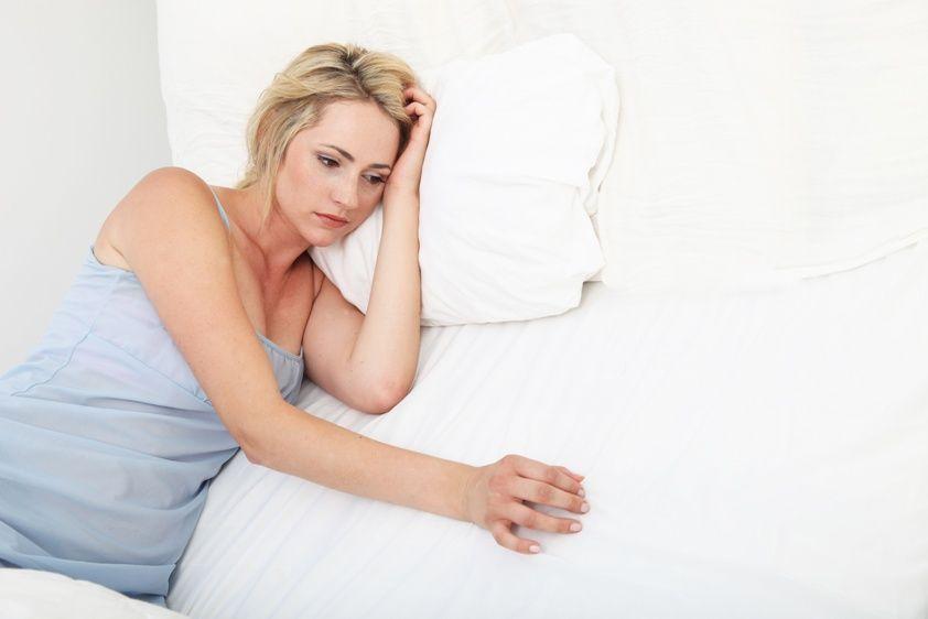 расстроенная женщина лежит в кровать