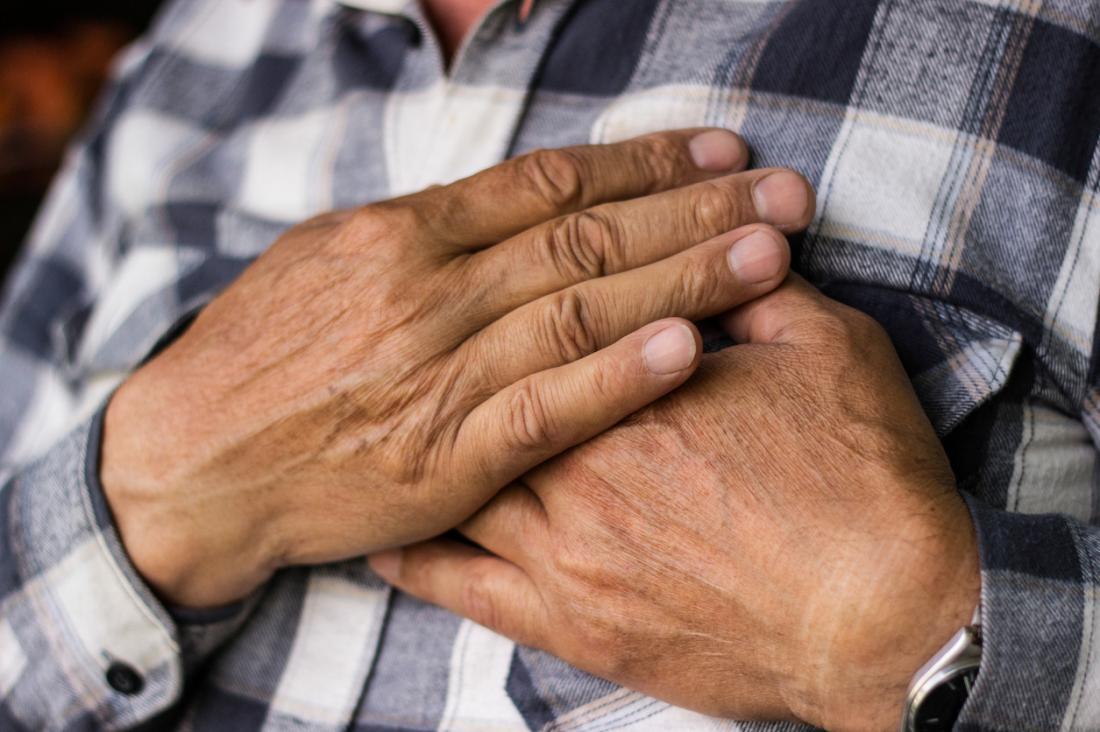 пожилой мужчина в клетчатой рубашке держится за грудь