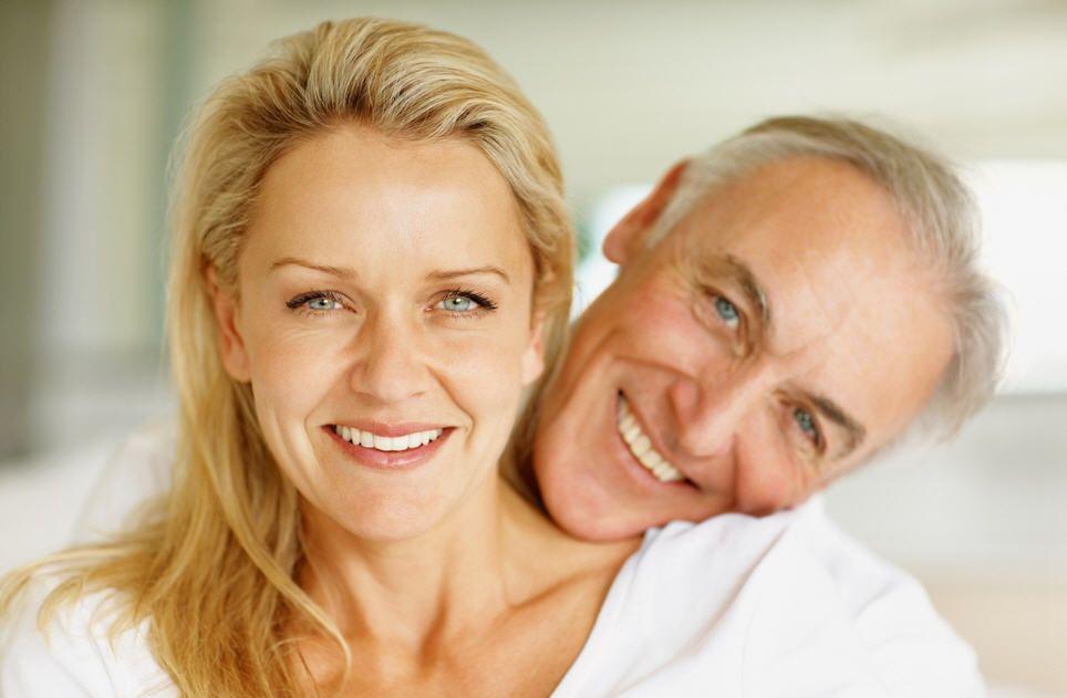 пожилые женщина и мужчина улыбаются в камеру