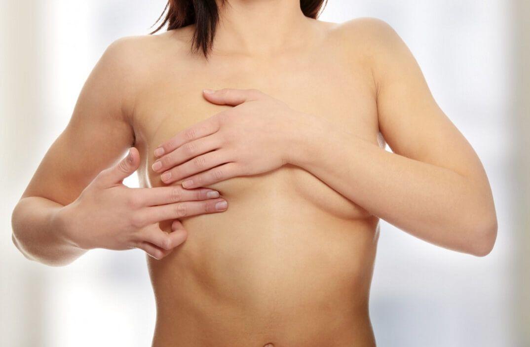 обнаженная женщина закрывает грудь руками