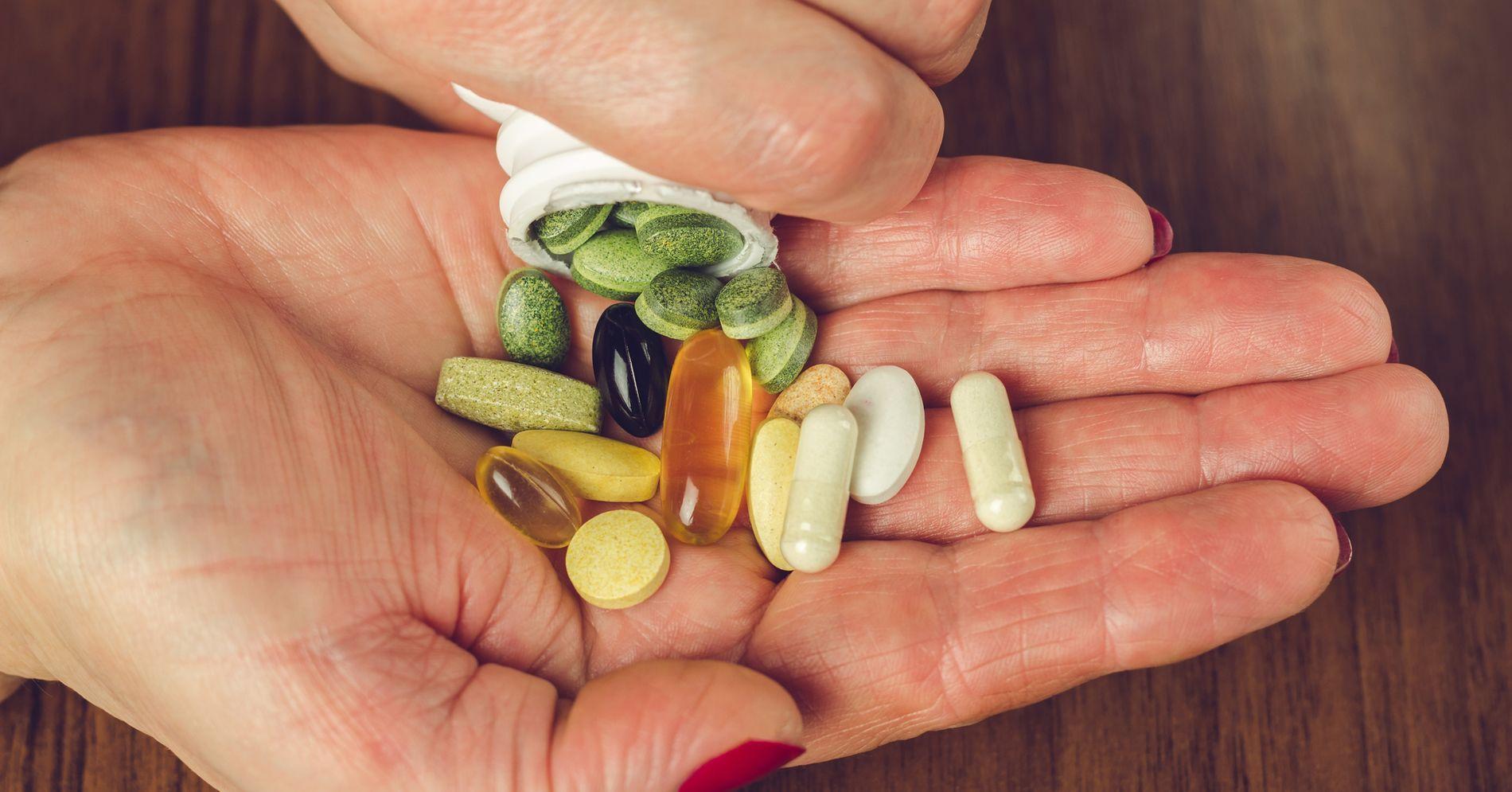 много разных таблеток на женской руке