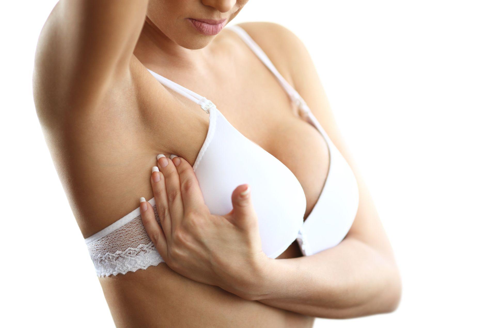женщина в белом бюстгальтере давит на грудь