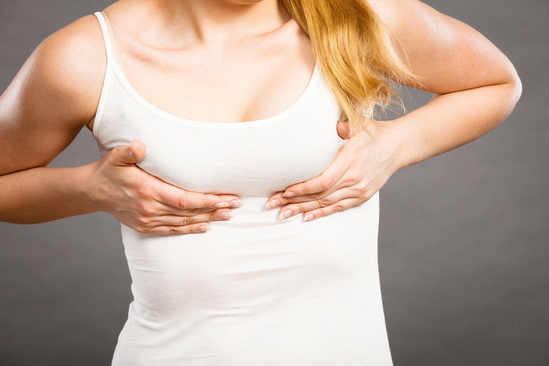 девушка в белой майке держится под грудью из-за ноющей боли