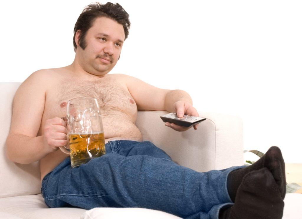 мужчина пьет пиво на диване