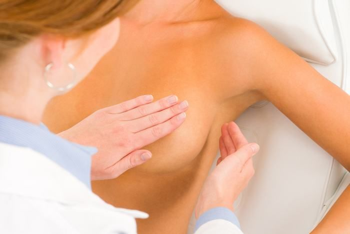 врач осматривает грудь женщины