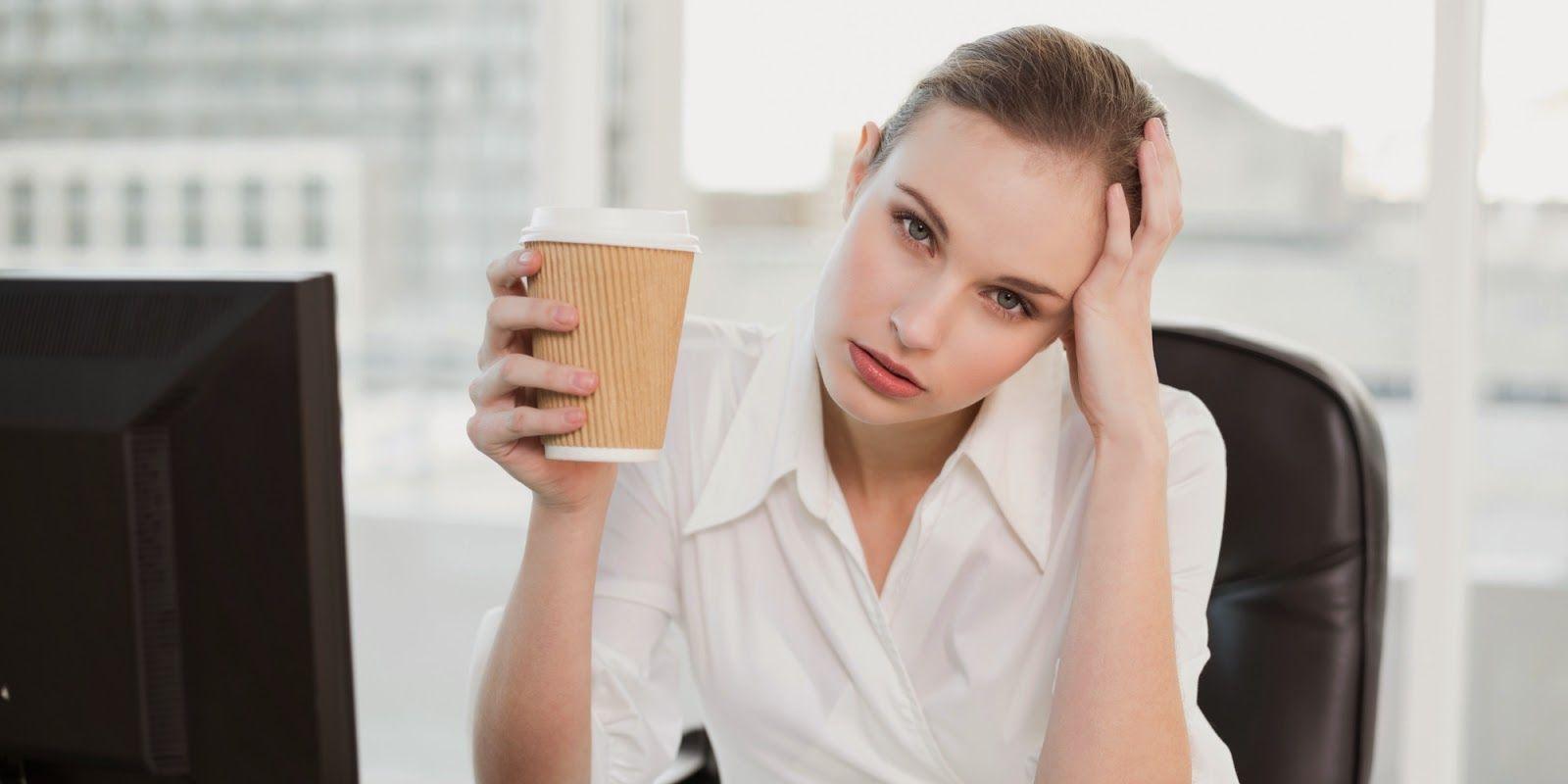 женщина в белой блузке дерд\жит в руке стаканчик кофе с собой