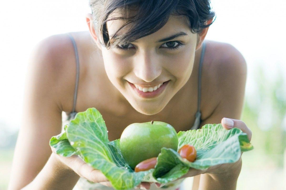 девушка держит в руках яблоко на капустном листе