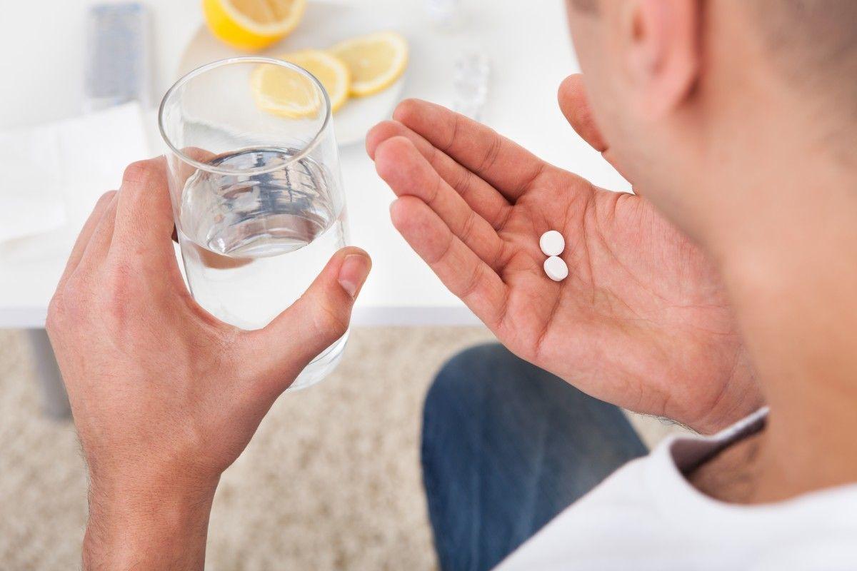 мужчина держит в руках две таблетки и стакан с водой