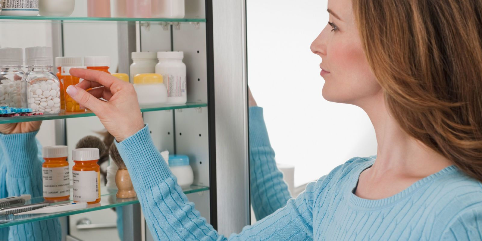 жженщина берет таблетки из шкафчика с лекарствами