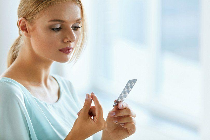 девушка смотрит на таблетки